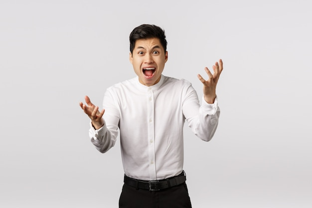 Outraged, alarmed young asian guy screaming what have you done, how could you, shaking hands in rage and anger, grimacing frustrated, disappointed with someone let him down