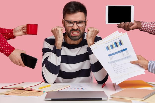 Outraged angry man has thick stubble, clenches fists in anger, unrecognizable people stretch hands to him with papers, mobile phone, notepad and mug