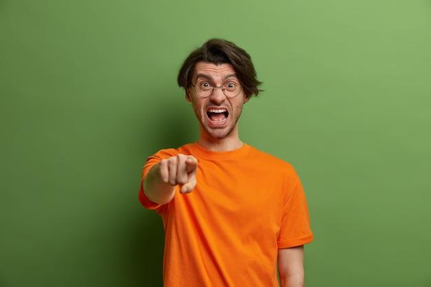 憤慨した怒っている男は大声で叫び、人差し指をあなたに向け、誰かが間違ったことをしたと非難し、否定的な感情を表現し、屋内でイライラし、カジュアルな服を着て、緑に隔離されます