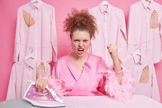 Indignata casalinga infastidita odio stirare stringe i pugni urla con rabbia ha i capelli ricci vestito con abiti domestici. il lavoratore di lavanderia irritato stira le camicie al salone di lavaggio a secco. concetto di pulizia