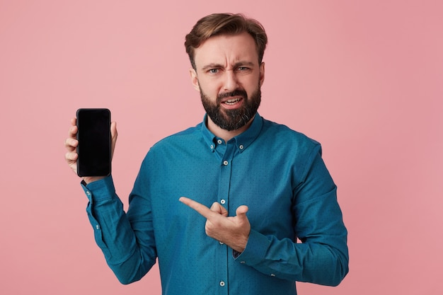 Outraged attractive bearded man, looking at camera and frowning, wearing a denim shirt, pointing with finger to his device. isolated over pink background.