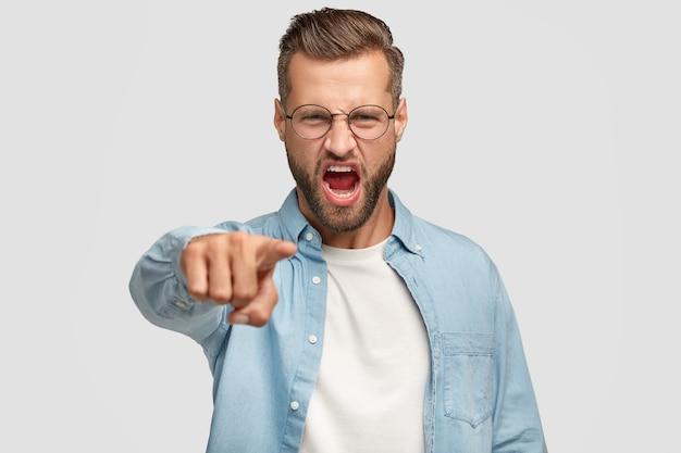 Возмущенный бородатый парень позирует у белой стены