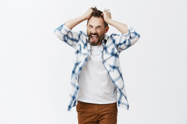 Outraged bearded mature man posing