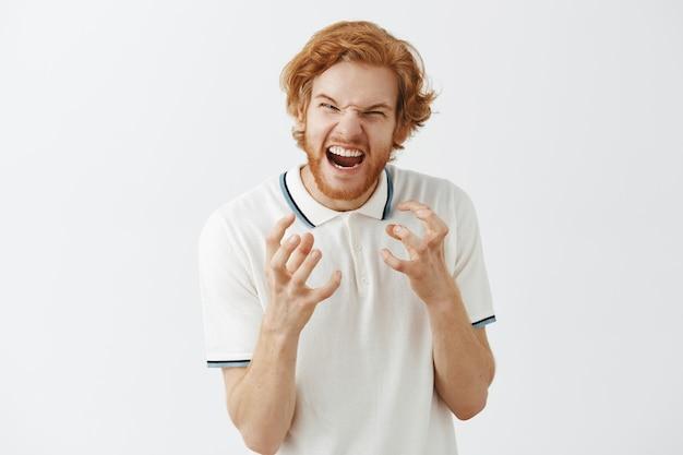 Ragazzo rosso barbuto indignato in posa contro il muro bianco