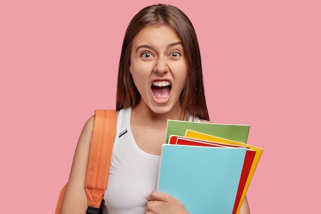 Una donna bruna oltraggiata esclama con rabbia, tiene la bocca ben aperta, si sente irritata dal pigro compagno di gruppo