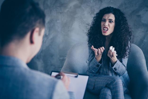 분노한 비즈니스 아가씨 앉아 회색 배경 위에 심리학자와 의자 이야기
