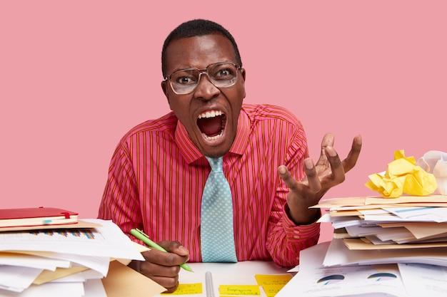 Возмущенный темнокожий бизнесмен сердито кричит, держит руку поднятой, одет в строгую рубашку, записывает информацию в блокнот