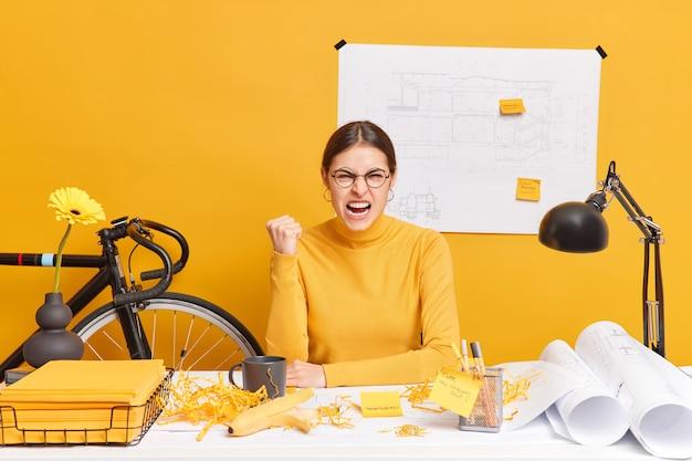 Возмущенная занятая офисная работница сжимает кулак, устав от подготовки инженерного проекта, сжимает кулак и сердито восклицает, позирует за рабочим столом с чертежами