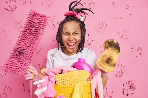 Outraged busy responsible housewife exclaims negatively has face smeared with mud holds sponge and mop busy cleaning house wipes dust engaged in housekeeping isolated over pink studio wall