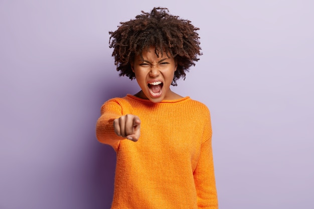 Outraged dark skinned female points index finger directly, has annoyed expression, says you are guilty, shouts with irritation, stands against purple wall. its he who offended me