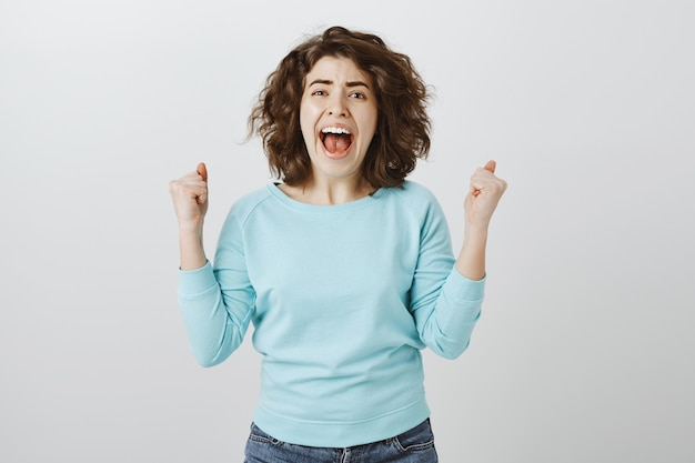 Outraged and distressed woman screaming and shaking fists