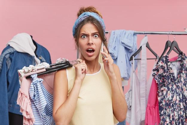 Donna oltraggiata che litiga per telefono, in piedi nel camerino con grucce di abiti, camicette e gonne contro gli opachi e cremagliera con vestiti