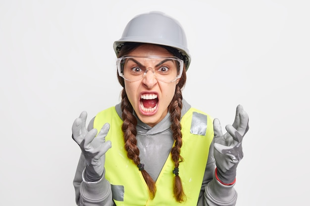 Outraged irritated female construction worker gestures angrily screams loudly being annoyed with partners who made big failure or mistake wears protective hardhat gloves safety glasses uniform