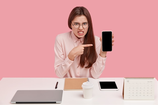 Outraged irritated young woman clenches teeth, points at empty screen of brocken cell phone, wears round spectacles and shirt, sits at workplace with laptop, calendar