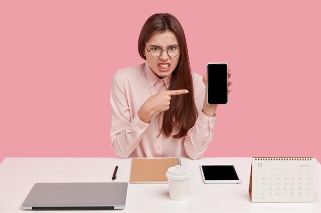 Indignata e irritata giovane donna stringe i denti, indica lo schermo vuoto del cellulare rotto, indossa occhiali rotondi e maglietta, si siede sul posto di lavoro con laptop, calendario