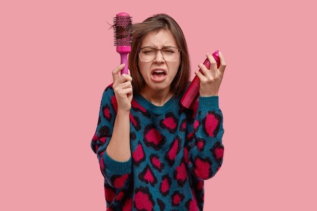 La donna nervosa indignata in preda al panico pettina i capelli, non può fare un taglio di capelli desiderabile, guarda disperatamente, urla negativamente, vestita con un maglione oversize