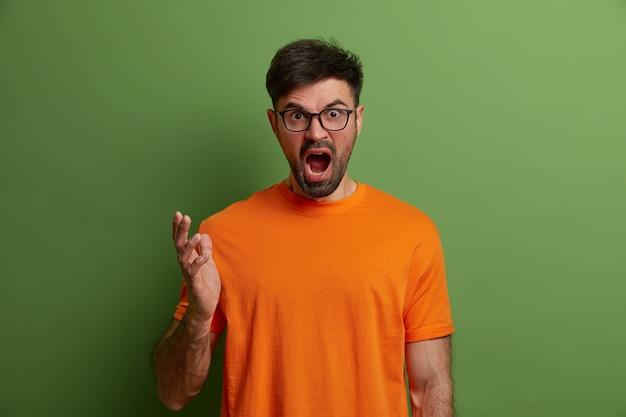 Uomo europeo stressante indignato urla per il fastidio, gesticola con rabbia, discute con qualcuno, perde la pazienza e si sente aggressivo, stringe la mano, indossa una maglietta arancione, isolato sul muro