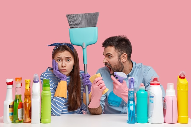 Indignato uomo con la barba lunga grida alla moglie, si lamenta di molto lavoro, trasporta spray e straccio, donna scontenta indossa la fascia, porta la scopa