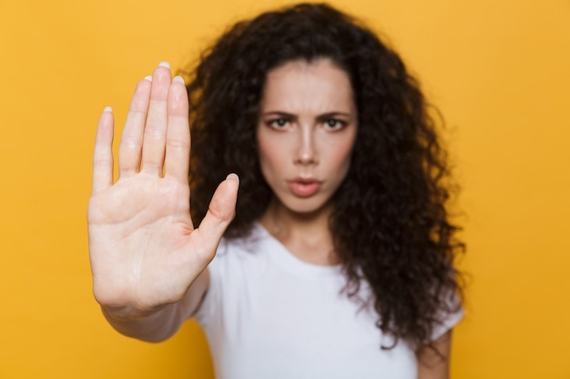 Outraged woman 20s with curly hair doing stop gesture with hand isolated on yellow