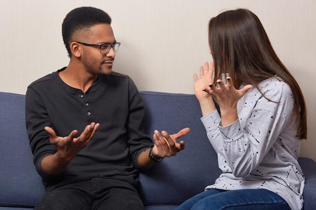 Возмущенные женщина и мужчина злобно жестят, смотрят друг на друга, ведут активный спор, не соглашаются с чем-то, чувствуют недовольство, высказывают свое мнение, садятся на удобный диван. многонациональная семейная пара утверждает