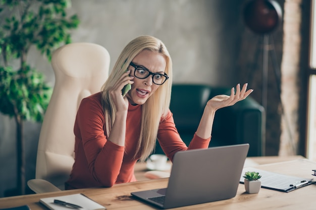 Outraged woman executive manager sit table use laptop read start-up project find mistake feel anger call employee  smartphone have argument shout office loft workstation red turtlneck