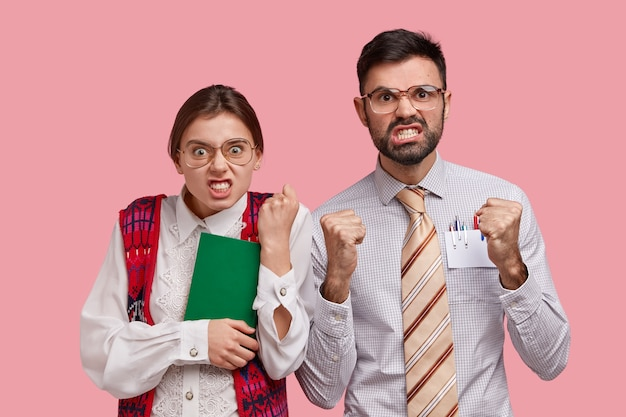 Outraged woman and man with annoyed expressions, clench fists and teeth, irritated to have much work, wear elegant clothes, dont agree with boss, isolated on pink wall. negative feelings