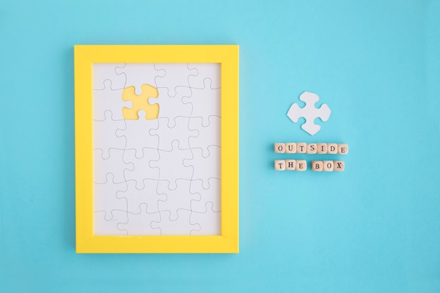 Outside the box blocks on yellow frame with white jigsaw puzzles