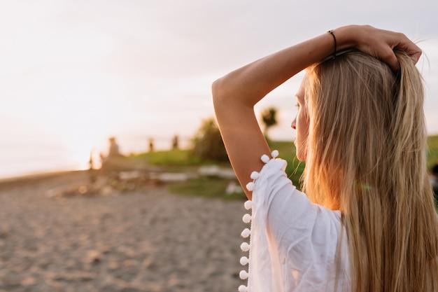 Снаружи крупным планом портрет молодой привлекательной женщины со светлыми волосами встречает рассвет на берегу океана