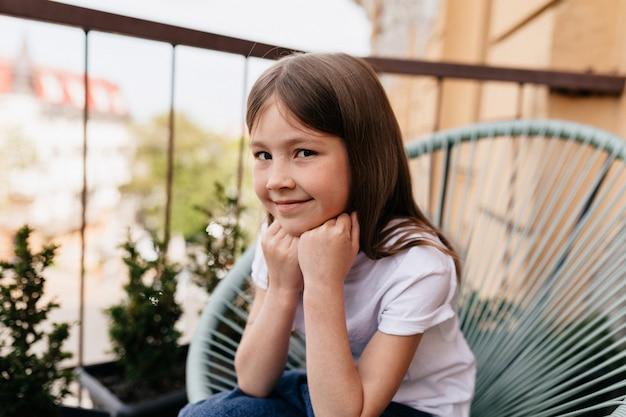 外のバルコニーに座っている素敵なかわいい女の子の肖像画を間近します。