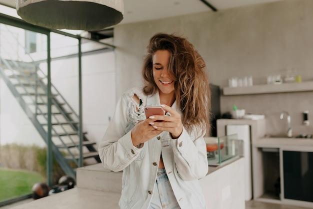Снаружи счастливый портрет очаровательной симпатичной улыбающейся женщины с кудрями, скручивающей смартфон в современном доме с летней террасой