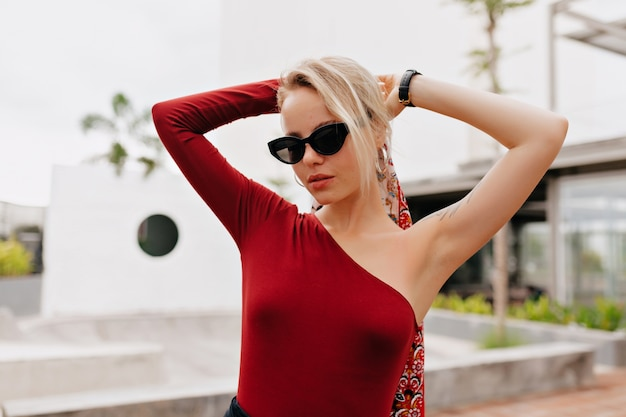 Ritratto esterno di attraente signora in rosso che tocca i suoi capelli e godersi la vita
