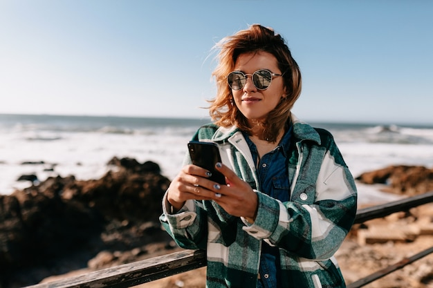 Outside portrait of attractive woman with curly short hairstyle wearing striped shirt using smartphone on shore of ocean with rocks