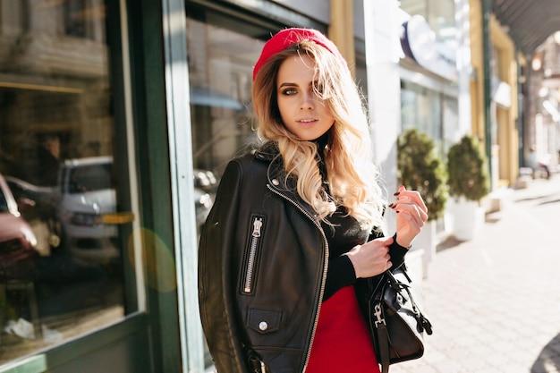 波状のブロンドの髪に身を包んだ赤いスカートと赤い帽子を持つ魅力的なきれいな女性の外の肖像画は、昼食から出てきて、日当たりの良い通りを歩きます
