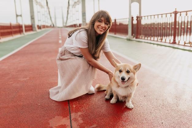 日光の下で街で犬と一緒に歩いている笑顔のきれいな女性の外の肖像画