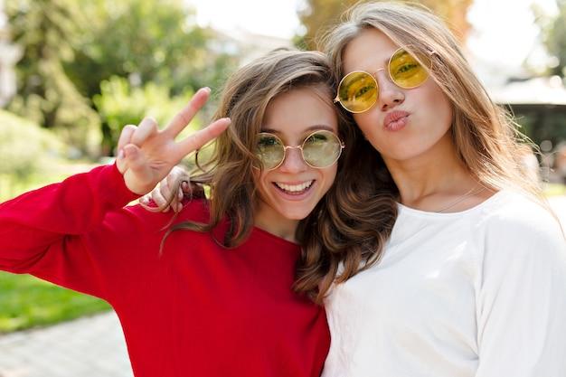 Ritratto esterno di due migliori amici che si divertono insieme sulla strada soleggiata nel parco, inviando baci e sorridendo con emozioni vere