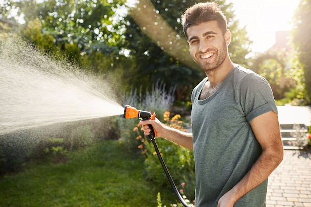 Ritratto esterno di giovane giardiniere caucasico attraente con barba e acconciatura alla moda in maglietta blu sorridente, annaffiare le piante con l'attrezzo da giardino, mattina d'estate produttiva.
