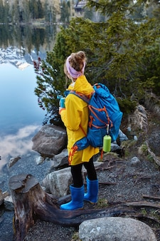 Outside shot of female traveler enjoys panoramic mountain lake, drinks hot tea during rest after strolling, carries big rucksack, has holiday trip