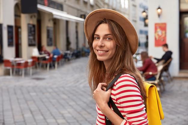 Inquadratura esterna di allegri turisti europei passeggia per le strade della città, porta lo zaino, indossa un cappello marrone e un maglione a righe