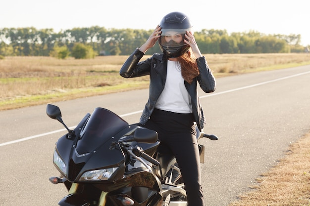 빠른 여성 오토바이의 외부 샷 보호 헬멧을 착용, 오토바이에 포즈, 오토바이에 서, 장거리를 커버, 잊을 수없는 여행이 있습니다. 사람, 승마, 안전 및 극한의 개념
