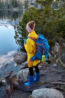 여성 여행자의 외부 샷은 파노라마 산악 호수를 즐기고, 산책 후 휴식 중에 따뜻한 차를 마시고, 큰 배낭을 들고, 휴가 여행을 가짐