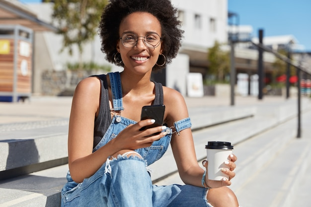 Outside shot of positive relaxed blogger with dark skin, chats online, uses free internet connection in city, enjoys aromatic takeaway coffee, wears glasses and overalls, poses at stairs with beverage