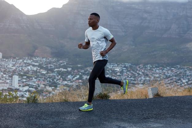 Inquadratura dall'esterno di un uomo sportivo dalla pelle scura in abbigliamento casual, corre veloce, copre lunghe distanze, modella sul paesaggio di montagna, vuole arrivare primo al traguardo. pose maschili etniche atletiche all'aperto