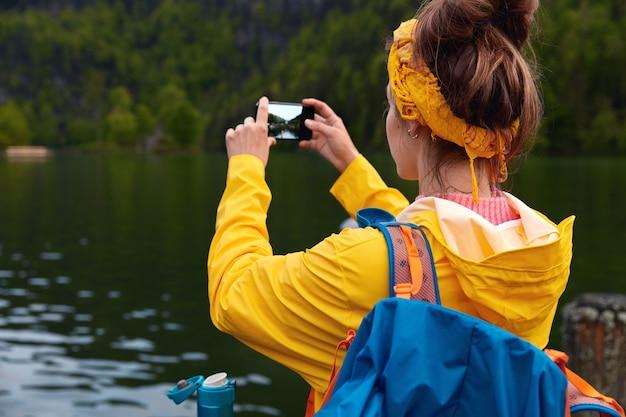 Colpo esterno del viaggiatore donna fa foto di un bellissimo paesaggio sul dispositivo smart phone, ammira il lago calmo