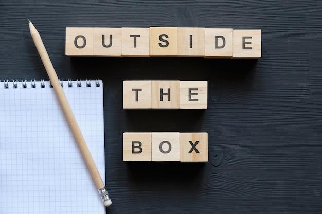 Модное слово современного бизнеса - outside the box на деревянных блоках