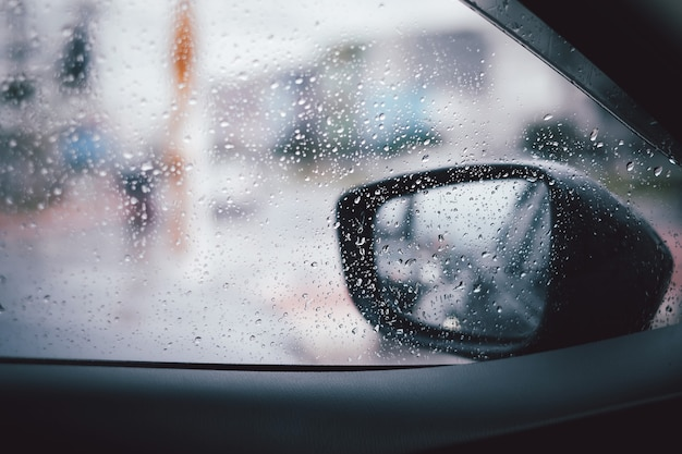 Outside view the fall rain make water droplets through the car and rear view mirror.