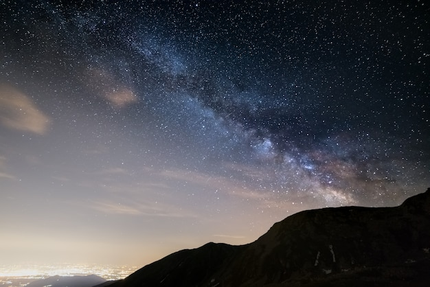 The outstanding beauty and clarity of the milky way and the starry sky captured from high altitude in summertime on the alps with glowing valley below and light pollution.