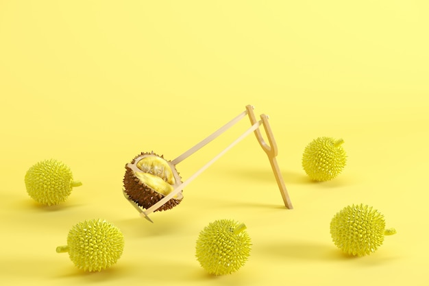 Outstanding fresh cut ripe durian in a slingshot surrounded on yellow background