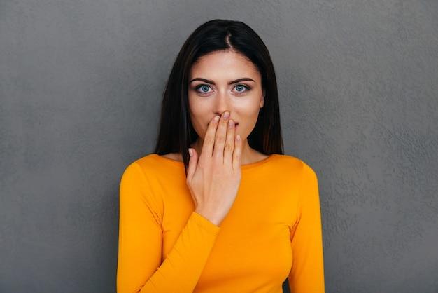素晴らしいニュース!手で口を覆い、灰色の背景に立ってカメラを見て驚いた若い女性