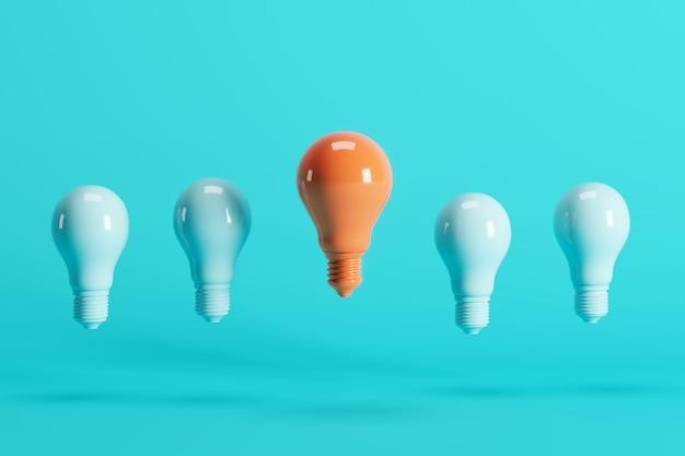 Outstanding orange light bulb among light blue light bulbs floating on blue