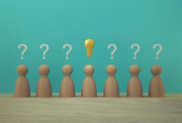Модель выдающихся бумажных людей со значком лампочки и символом вопросительного знака